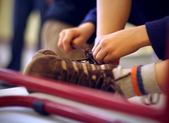 Boy trying to tie his shoes.