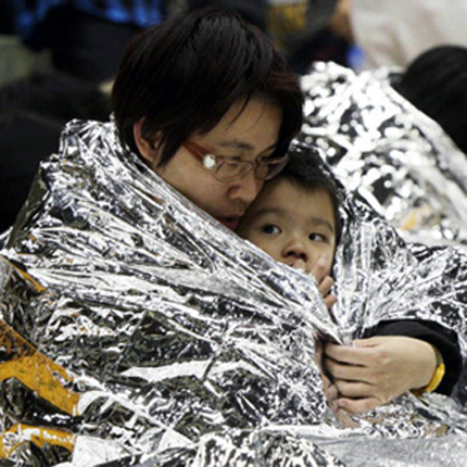 Parent and Child in Japan bundle in an emergency blanket following disaster