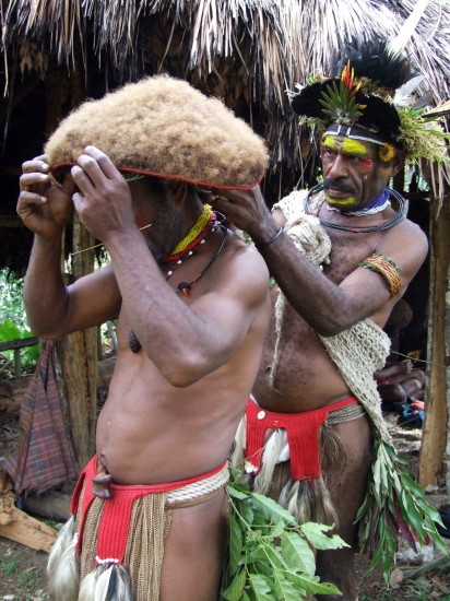 A Huli Wigmaster put the finishing touches on a wig, New Guinea.