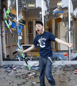A Canucks fan holds a hockey stick after smashing the windows of a bank as he reacts to the Canucks losing the NHL Stanley Cup to the Bruins in Vancouver