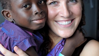 Christina Fast holds one of her patients during service in Guinea