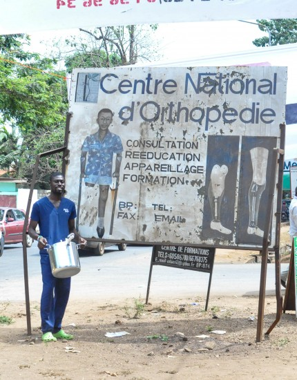 Fellow Mercy Ships volunteer stands outside the sign of the National Orthopedic Clinic with a pressure cooker
