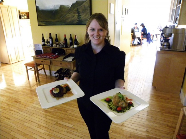 Our waitress Sheena holding our orders of house-made Strozzapreti and Cumin Crusted Cod.