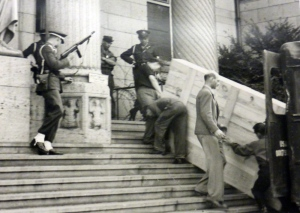 Theodore Heinrich, in light-coloured civilian dress, is shown receiving art at a depository for recovered lost or stolen art run by the U.S. Army. The photo was taken around 1949 in Wiesbaden, Germany. (University of Regina archives)