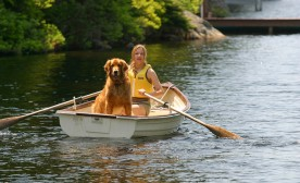 Girl in Row Boat with Golden Retriever