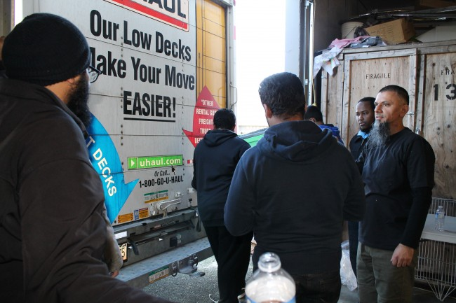 Faizel Kathrada (right) watches as small trucks arrive from various sources with goods destined for Refugees in Syria.