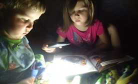 Reading little brother a bedtime story by flashlight in the tent
