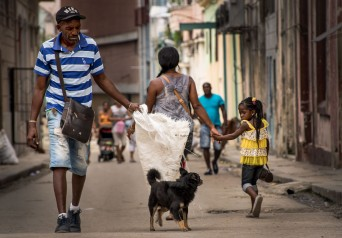 While crossing paths on the streets of Havana, a little girl and dog share a moment