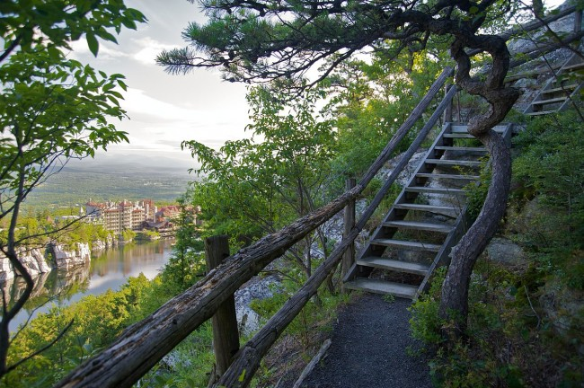 A branch of one of many hiking trails leading up to a gazebo seen against guest rooms in the far background across Lake Mohonk at Mohonk Mountain House