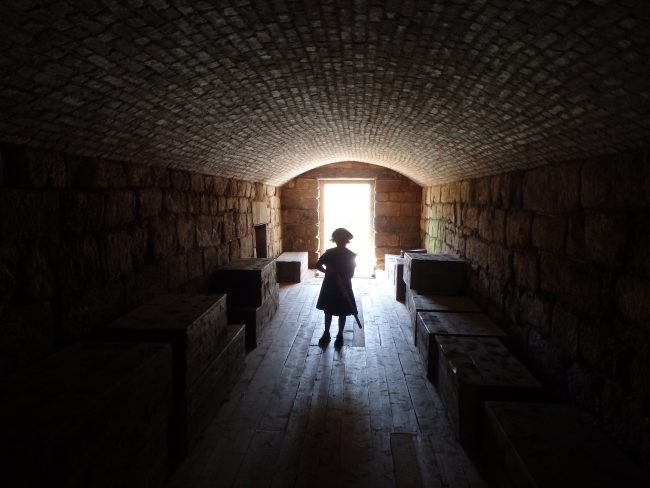 A young boy in period costume enters Fort Beausejour's spooky tunnels