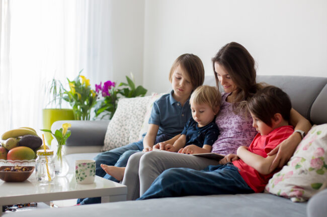 Young woman, mother with three kids, reading a book at home, hugging and laughing